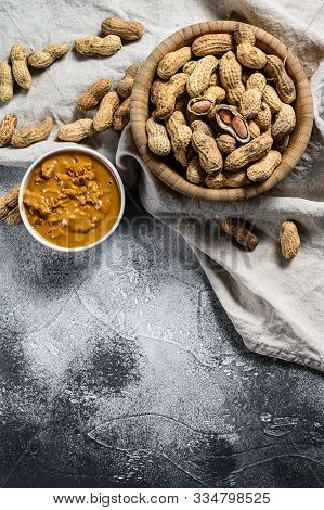 Peanut Butter In A Bowl, Raw Peanuts. Vegetarian Food. Gray Background. Top View. Space For Text