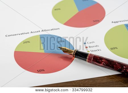 Expensive Gold Fountain Pen Pointing To Conservative Asset Allocation Pie Chart On Desk