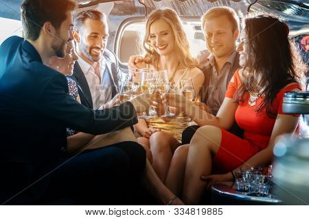 Group of women and men clinking glasses in a limousine having fun and being happy