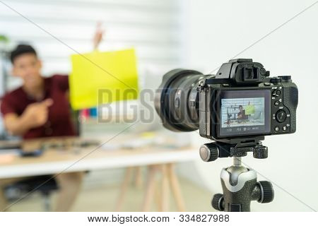 Young asian male online merchant blogger recording live vlog video with colorful shopping bag preparing for sale and review goods at home. Online influcencer on social media concept. Focus on camera