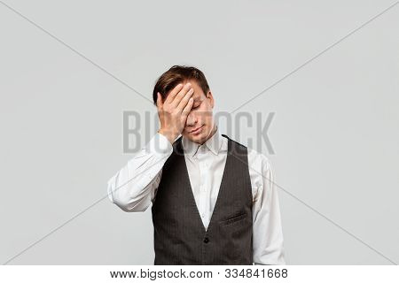Tired Young Business Man Holding Hand On Head Covering Face Isolated Over Grey Nackground. Stress On