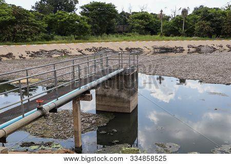 Sewage Water Treatment Pond - Bridge To Sediment Pond With Defocused Blur Background