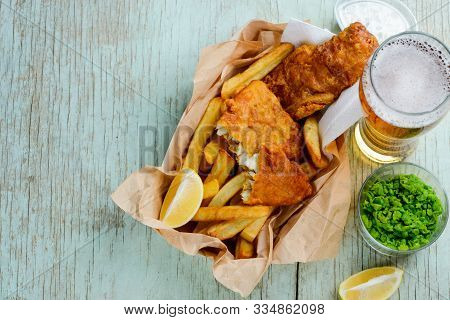 Deep Fried Fish And Chips With Lemon Slices, Green Peas And Beer