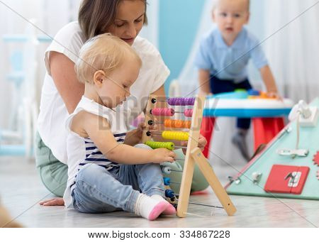 Kids Playing On Floor With Developmental Toys In Kindergarten. Children Have Fun In Nursery Or Dayca