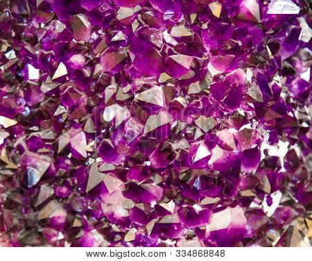 Amethyst purple crystal. Mineral crystals in the natural environment. Texture of precious and semiprecious gemstone. Gems