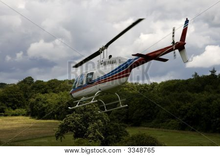 White Helicopter In Flight Over Trees
