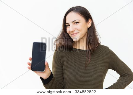 Happy Cheerful Cellphone User Showing Blank Screen. Young Woman In Casual With Mobile Phone Standing