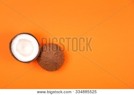 Top View Of Haved Ripe Coconut On Russet Orange Background. Summer Concept. Minimal Flat Lay.place F