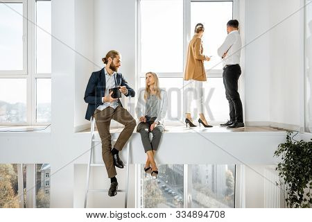 Group Of A Young Creative Office Employees Having Some Informal Discussion, While Standing In The Tw