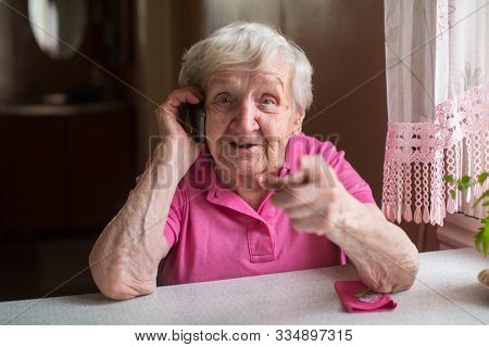 Elderly woman talking on a mobile phone sitting at a table in his house.