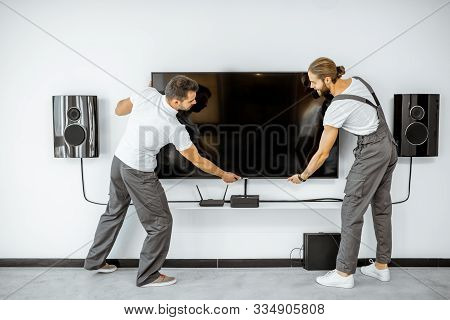 Two Professional Workmen In Workwear Installing A Large Tv Monitor And Audio System In The White Liv