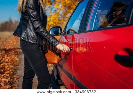 Opening Car Door. Woman Opens Red Car With Key On Autumn Road. Driver Ready To Go