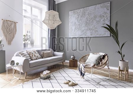 Modern And Bohemian Composition Of Interior Design With Gray Sofa, Rattan Armchair, Wooden Cube, Pla