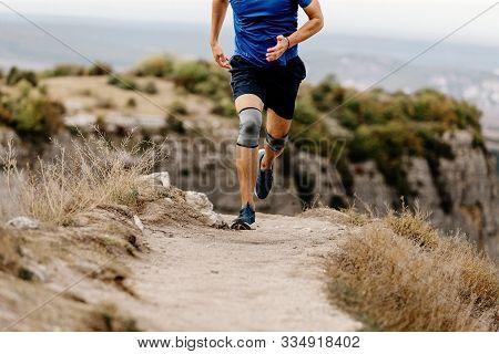 Athlete Runner Knee Injury Run In Knee Pads On Mountain Trail
