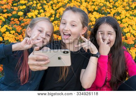 Three Teen Girls Take A Selfie On Iphone Xs On A Sunny Day And Laugh. Girls Are Showing Victory Sign