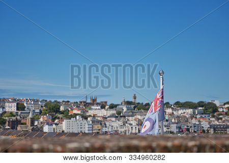 View Of A Flag And St. Peter Port From Castle Cornet In St Peter Port, Guernsey, Uk
