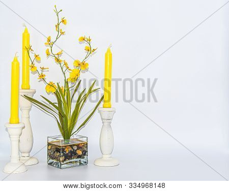 Primary Color Yellow Still Life Of Candles And Artificial Flowers On White Background.