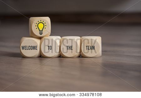 Cubes And Dice On Wooden Background With The Message Welcome To The Team And Lightbulb
