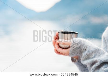 Woman With Mug Of Coffee By Winter Sea, Blue Mountains. Cozy Picnic With Thermos Of Hot Steamy Bever