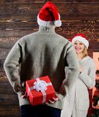 Generosity and kindness. Surprising his wife. Prepare surprise for darling. Winter surprise. Man carry gift box behind back. Woman smiling face santa. Christmas surprise concept. Giving and sharing poster