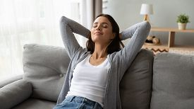 Relaxed Serene Young Woman Lounge On Comfortable Sofa At Home
