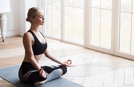 Yoga Girl With Closed Eyes Sitting In Lotus Pose And Meditating In Yoga Studio, No Stress Concept, C