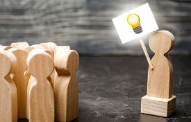 A Person With An Idea Light Bulb Sign Agitates A Group Of People. The Concept Of Proposing New Fresh