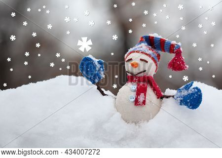 Snowman Toy With Hat Red Scarf And Blue Mittens On Snowy Field Background. Happy New Year And Merry