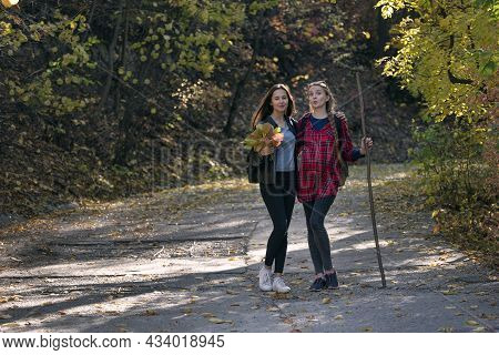 Two Young Girls Stand And Grimace In The Autumn Park And Enjoying Sunny Day.
