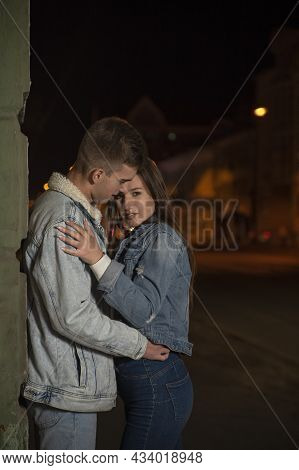 Young Couple Hugs On Evening City Background. Beautiful Young Couple In Love. Romantic Date On The S