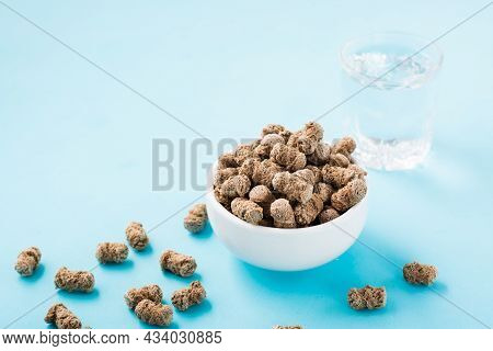 Rye Bran In A Bowl And On The Table And A Glass Of Water On A Blue Background. Diet And Cleansing Th