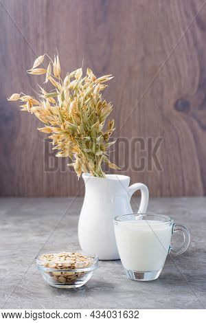 Oat Milk In A Cup, Oatmeal And Ears Of Corn In A Jug On The Table. Alternative To Cow's Milk. Health