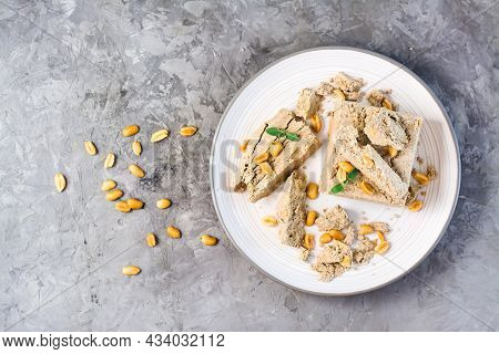 Pieces Of Sunflower And Peanut Halva And Mint Leaves On A Plate And Nuts Nearby On The Table. Calori