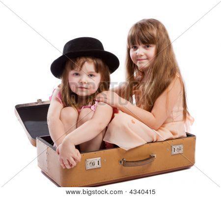 Girls Sitting In Suitcase