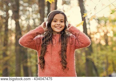 Happy Kid Relax In Autumn Nature. Small Girl Wear Headphones. Modern School Education. Child Listen