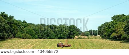 Rows Have Been Cut In The Hayfield And The Farmer Is Making The Last Trip Across This Scenic Pasture