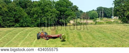 The Farmer Checks Out The Freshly Cut Grass In The Hayfield.