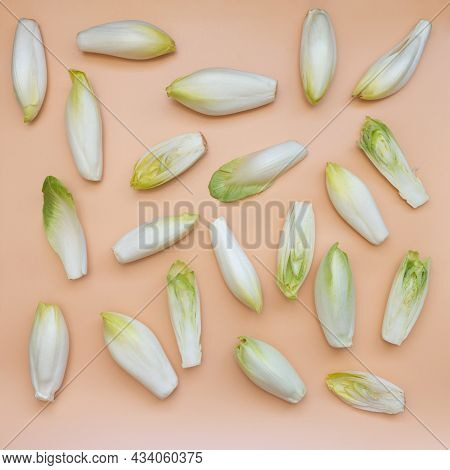 Many Raw Endives Salad Roots Or Chicory On Light Orange Background, Top View, Healthy Organic Meal C
