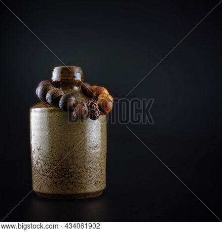 A Wooden Scented Bracelet On An Old Rum Ceramic Bottle Against A Black Background With Copy Space
