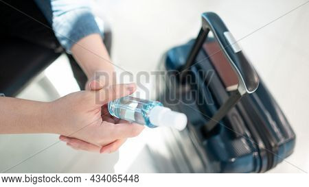 Cleaning Suitcase Luggage Handle With Hand Sanitizer Spray. Male Tourist Preparing Antibacterial Pro