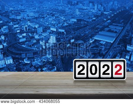 Retro Flip Clock With 2022 Text On Wooden Table Over Modern Office City Tower, Street, Expressway, A