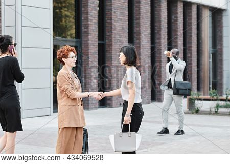 Horizontal Medium Long Shot Of Mature Caucasian And Young Asian Co-workers Greeting Each Other With