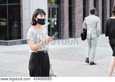 Horizontal Medium Portrait Of Young Asian Woman Wearing Protective Mask On Face Holding Smartphone S