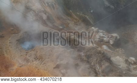 Water Boils In A Geyser. Steam Rises Over The Mountainside. Sulfur Deposits On The Soil. Close-up. V