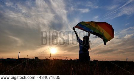 Bisexual, Lesbian, Woman, Transgender Holds Lgbt Flag On A Background Of The Sky At Sunset And Celeb