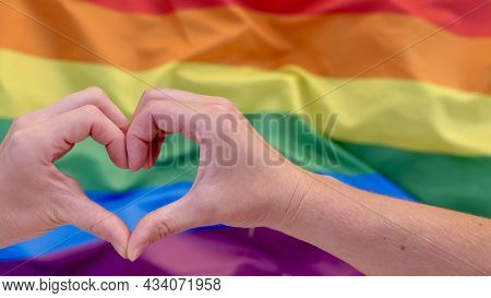 Young Lesbian Couple Holding Hands On Heart Shaped Rainbow Lgbt Flag Background. Female Homosexual C