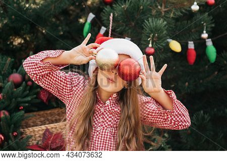 Merry Christmas. Portrait Of Happy Funny Child Girls In Santa Hat With Christmas Tree Toys Near Face