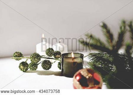 Green Scented Christmas Candle And White Wax Candles Next To Pine Branch And Red Christmas Ball. Hol
