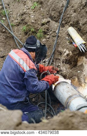 Plumber Standing In Pit Is Engaged In Elimination Of Communal Accident Outdoors. Utility Worker Fixi