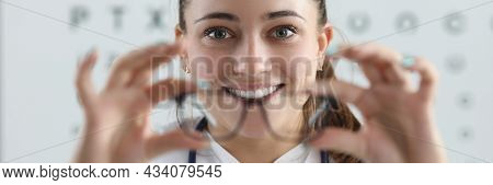Woman Ophthalmologist Gives Glasses For Fitting On Background Of Table For Measuring Vision